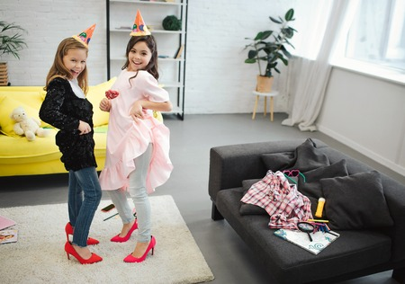 Two teenage girls have fun together in room. They dance and pose on camera. Brunette hold lollipop in hand.