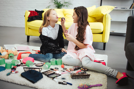 Brunette girl sitting on carpet in room with her friend and putting lipstick on her lips. Blonde teenager concentrated.