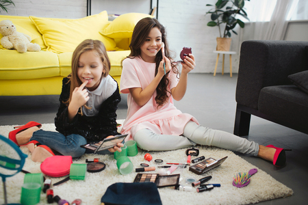 Cheerful ans exited girls sitting on floor in room. They doing makeup. Teenagers look in mirror and use cosmetics.