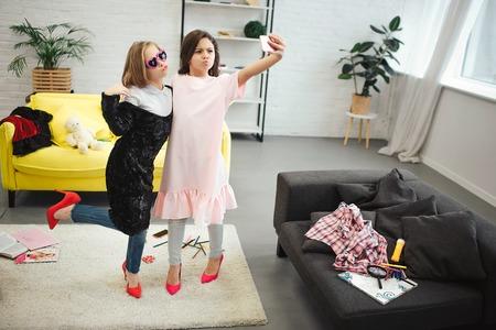 De jeunes adolescents élégants se tiennent dans la chambre et posent sur la caméra du téléphone. Ils portent des vêtements pour femmes adultes. Brunette tenir la caméra. Ils prennent selfie. Banque d'images