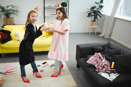 Two teenagers have fun. They stand in room and hold one gift together. Girls wear clothes and shoes for adult women. They have birthday party. Stockfoto