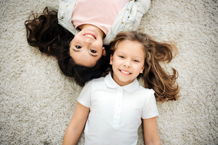 Picture of two girl lying on carpet and look straight. They smile and pose. Friends lying head to head. Isolated on grey background.