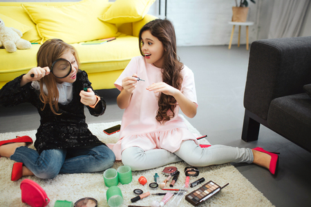 Two teenagers sitting on carpet in room together. Girl on left look at bottle through loop. Her friend put some nail polish. They are busy.