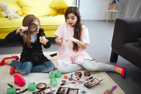 Two teenagers sitting on floor in room. Girl on left look at bottle through lenz. Teenager on right put some nail polish. She looks amazed.