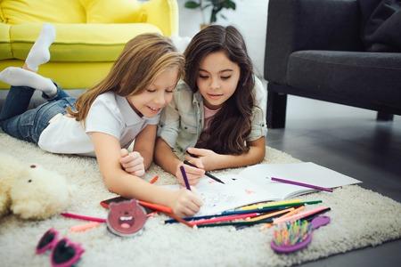 Deux adolescents occupés allongés sur de la moquette dans la chambre. Ils dessinent. Banque d'images