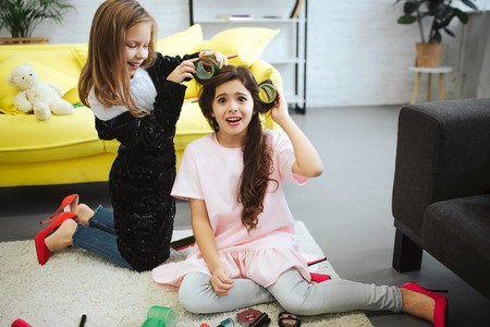 Amazed small girl look on camera. She suffer from pain. Her friend stand on knees and wrap hair on curler. She has fun. Girls wear clothes for adult women.