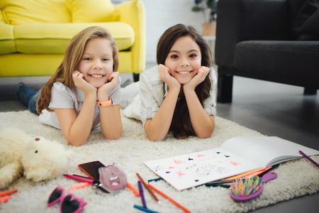 Deux jeunes adolescents joyeux allongés sur un tapis et posent devant la caméra. Les filles ont l'air droites et sourient. Ils dessinent sur papier. Les filles se tiennent la main sous le menton.