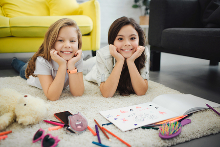 Two cheerful young teenagers lying on carpet and pose on camera. Girls look straight and smile. They draw on paper. Girls hold hands under chin. 写真素材