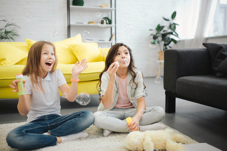 Young girls sitting on floor and having fun. Brunette making luftbolper. Another teenager try to catch them. She rejoice.