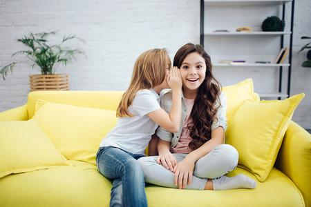 Des adolescents heureux et excités sont assis sur un canapé dans la chambre. La première fille chuchote à l'oreille de son amie. Sourire d'adolescent brune.