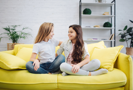 Happy and positive young teenagers sit on yellow sofa and look at each other. Girls keep legs crossed. They talk.