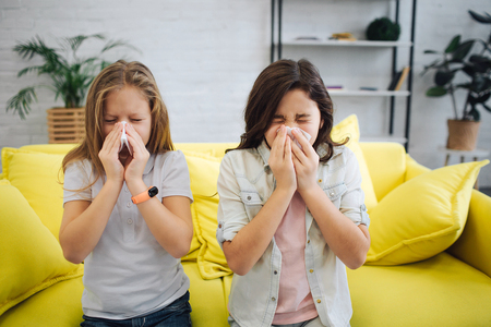 Two sick teenagers stand in room and sneeze. They hold white tissues in hands. Gitls suffer. They sick. Stockfoto