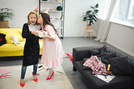 Happy small blonde girl hold present from her friend. Brunette kissing her in cheek. Teenagers wear clothes and shoes for adult women. They look happy in room.