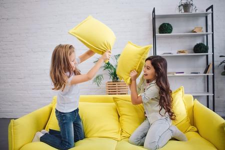 Deux adolescents joyeux ont une bataille d'oreillers sur un canapé dans la chambre. Ils se tiennent à genoux l'un en face de l'autre.