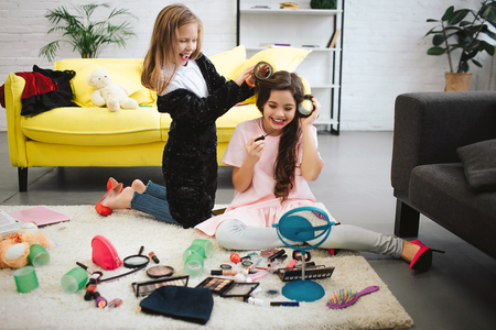 Two happy teenage girls having fun in room. They sit and stand on carpet. Blonde girl curling her friends hair. Brunette doing makeup and look in mirror. She smiles. Stockfoto