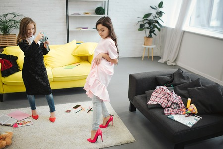 Small blonde girl taking picture of her friend on camera in room. Brunette posing and looking down. Both teenagers wear clothes and shoes for adult women. Imagens