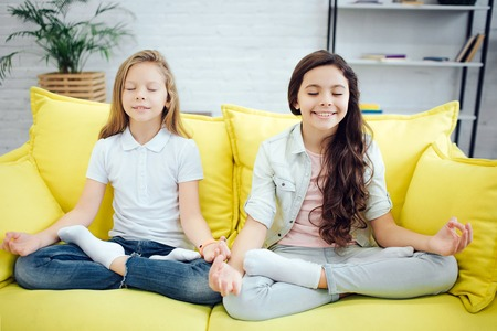 Two young teenagers sit in lotus pose on yellow sofa in room. They meditate. Girls express positive emotions. They keep eyes closed. 写真素材