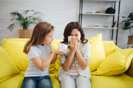 Sick girl on righht sit on sofa and sneeze. She suffer. Girl on left give her white cup. She try to help her. They sit on yellow sofa in room.