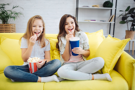 Two excited teenagers sit on sofa and watch forward. They hold busket with popcorn and cup of coke. Girl keep legs crossed. They smile and joy Banque d'images