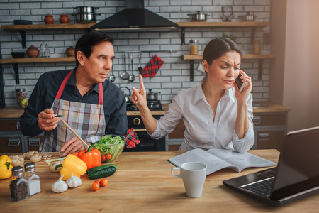 Busy woman sit at table and talk on phone. Man look and lean to her. They sit at table in kitchen. Guy interrupt woman. She is irritated.