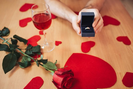 Picture of woman hands holding box with proposal ring on table. Red rose and heart shapes lying there Foto de archivo