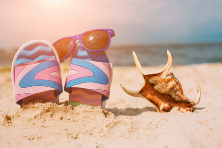 Flip-flops in sand on beach. Sunglasses on it. Summer vacation concept. Sea shore. Paradise. Sea shell lying on sand. Banco de Imagens - 115900126