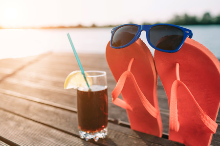 Concept of luxury vacation. Cola in glass on wooden pier. Pink flip flops with sunglasses on it. Beach party. Clear blue sky. Horizontal, wide screen format.