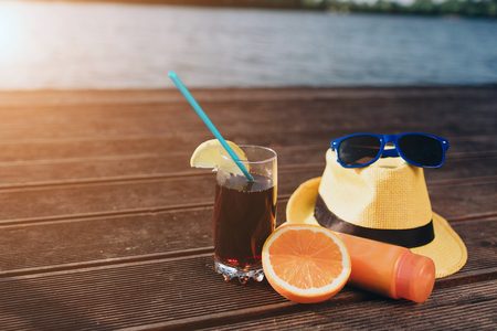 Concept of luxury vacation. Cola on the pier. Summer hat, sunblock cream, citrus, cola near the water. 版權商用圖片