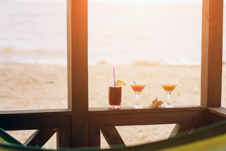 Fresh exotic cocktails on wooden edge. Shell lying between glasses. Cola with straw and lemon. Edge of house. View at ocean.