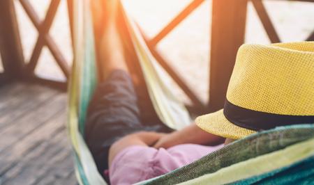 Giovane che si trova in amaca alla spiaggia soleggiata dall'oceano e dorme. Ha tenuto sul viso. Giovane agghiacciante.
