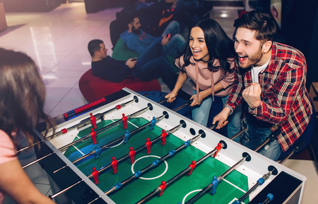 Happy young man and woman playing together in room. Intense game. Winning and loosing. Opponents at table soccer Stok Fotoğraf