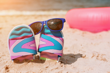 Flip-flops in sand on beach. Sunglasses on it. Summer vacation concept. Sea shore. Paradise. Pink swimming ring lying behind on sand.