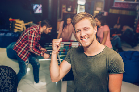 Happy young man stand in playing room and pose on camera. He smile and hold hand in fist. His friends playing table soccer behind.