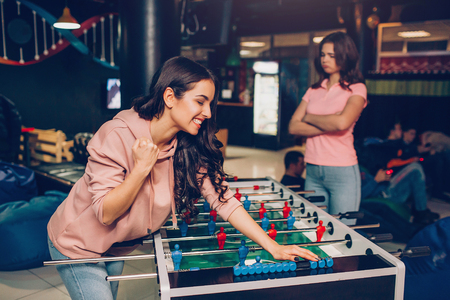 Happy young brunette lean to table soccer in playing room. Her friend is upset. She hold hands crossed.