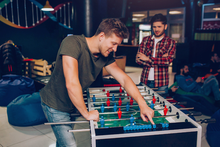 Happy young man stand and lean at table soccer in playing room. His unhappy friend stand behind. He hold hands crossed. Stok Fotoğraf