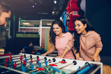 Playful excited young women playing table soccer with guy in room. Models loook at game and control it. Stok Fotoğraf
