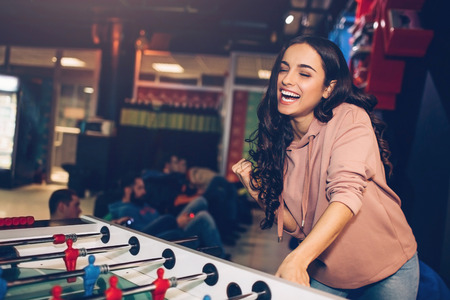 Young attractive woman stand in playing room and play table soccer. She smile. Model hold hand on playing arm. She looks happy. Men behind sit. Stok Fotoğraf
