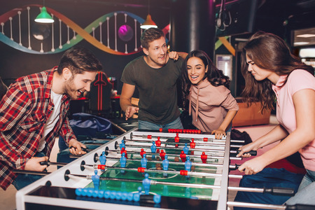 Enthusiastic excited young man and woman playing table soccer in room. Their friends stand beside and cheer. Stok Fotoğraf
