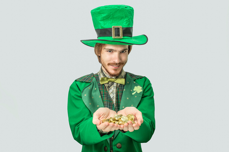 Young redhead man holding lots of golden coins in hands and show them to camera. He look straight forward. Guy wear saint Patricks suit. Isolated on grey background. Stock Photo
