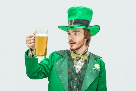 Amazed young man in green saint Patrick suit holding mug of beer and look at it. He is amazed. Isolated on grey background.