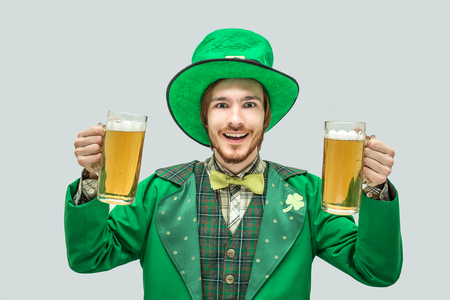 Happy positive young man in green saint patrick suit holding two big mugs of beer and smile. Isolated on grey background. Stock Photo