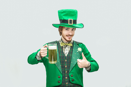 Happy young man in saint Patrick suit hold mug of beer and look on camera. He hold big thumb up. Isolated on grey background.