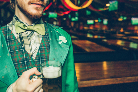 Cut view of man in green saint patrick's suit stand in pub and hold mug of beer. Guy is alone in room Zdjęcie Seryjne