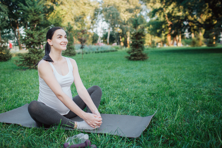 Cherful nice young woman stretching legs on yoga mate outside in park. She smiles and hold hands on feet Stockfoto