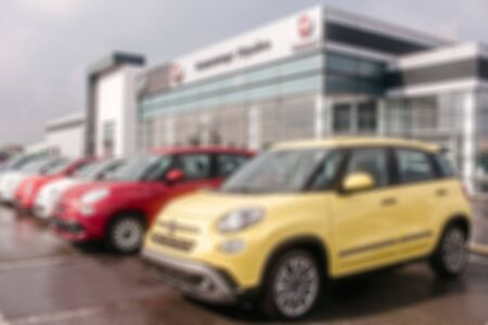 Kiev, Ukraine - September 11, 2018. Unclear picture of Fiat cars standing outside close to dealer building. There is yellow car in front of picture. Red and white ones are behind it. It is cloude outside.