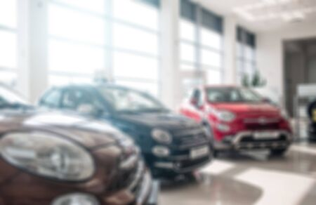 Kiev, Ukraine - September 11, 2018. Brown, red and blue with green cars stand in salon with glass walls. It is sunny and bringht inside. There is nobody in salon near Fiat cars. Blur and not focus