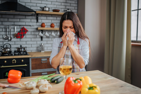 Young woman sit at table in kitchen and snezing. She caught cold. Sick model cover mouth woth napkin. Vegetables lying on table.