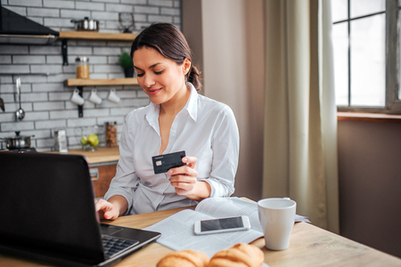 Nice cheerful woman sit at table in kitchen. She work at home. Woman hold black credit card nd type on laptop keyboard. Phone, cup and plate with croissans on table.