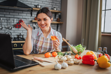 Nice positive woman sit at table in kichen. She talk through headphones and wave to laptop screen. Woman happy. Vegetables lying on table.