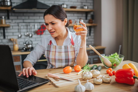 Disturbed woman sit on table in kitchen. She hold glass of wine and type on keyboard. Model look on laptop screen. She is emotional.